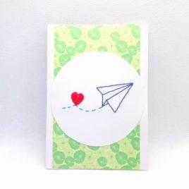 Carte brodée, avion en papier.